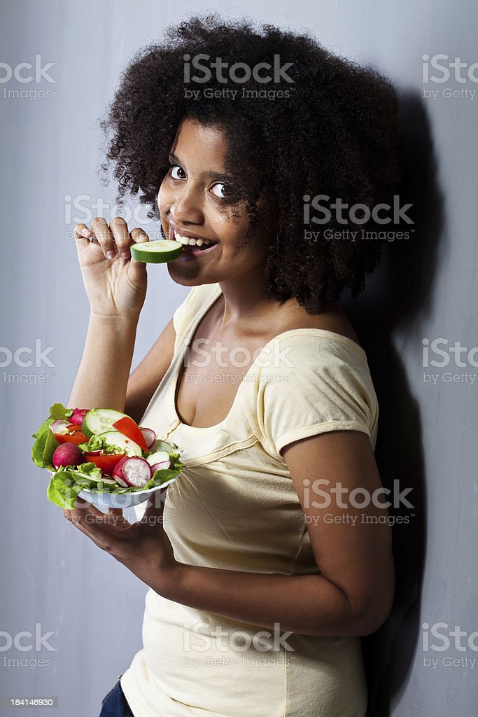 African Descent female eating salad royalty-free stock photo