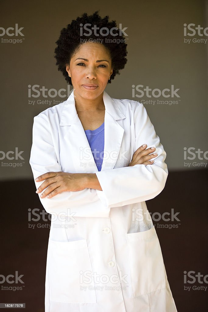 African descent female wearing lab coat arms crossed stock photo