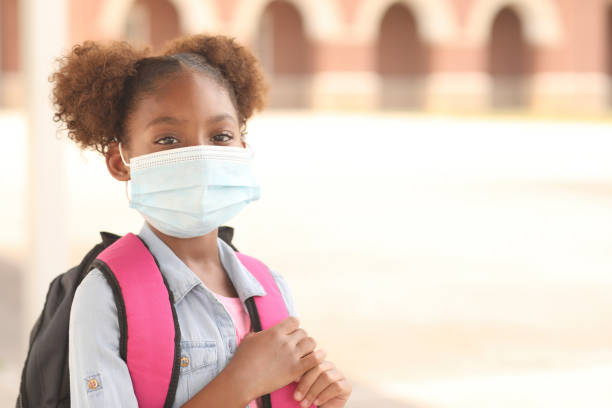 African descent, girl on school campus. Mask for COVID-19. Back to school. African descent girl on school campus. She wears a mask for COVID-19, Coronavirus protection. school building stock pictures, royalty-free photos & images