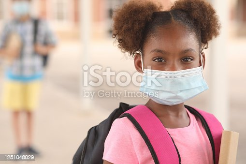 Back to school. African descent girl on school campus. She wears a mask for COVID-19, Coronavirus protection. Other student in background.