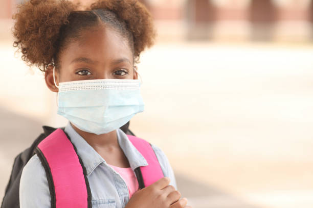 African descent, girl on school campus. Mask for COVID-19. stock photo