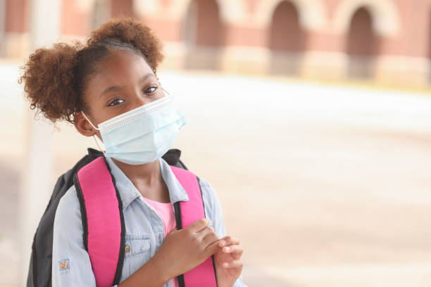 African descent, girl on school campus. Mask for COVID-19. Back to school. African descent girl on school campus. She wears a mask for COVID-19, Coronavirus protection. covid-19 stock pictures, royalty-free photos & images