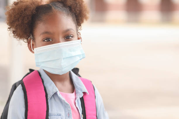 African descent, girl on school campus. Mask for COVID-19. Back to school. African descent girl on school campus. She wears a mask for COVID-19, Coronavirus protection. covid stock pictures, royalty-free photos & images