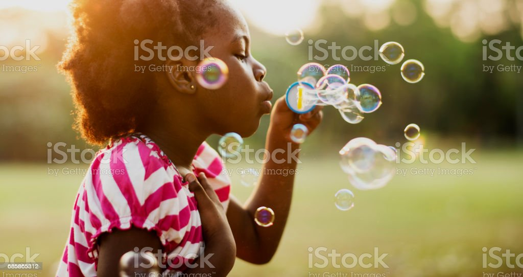 African descent girl playing blowing bubble in a park – Foto