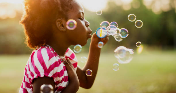 African descent girl playing blowing bubble in a park stock photo