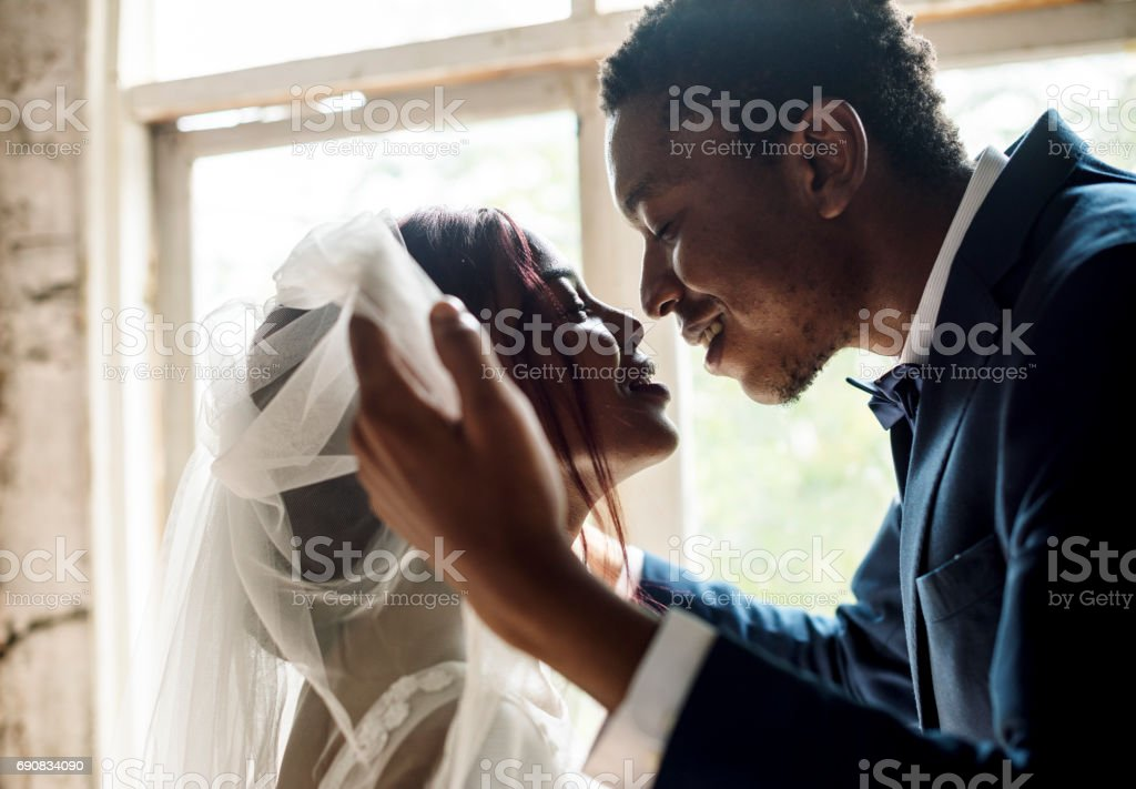 African Descent Groom Open Bride Veil Wedding Celebration stock photo