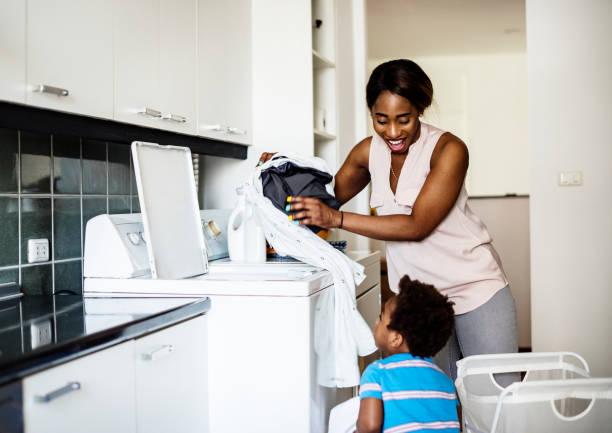 洗濯をしているアフリカ系の子供支援母親 - 衣類乾燥機 ストックフォトと画像