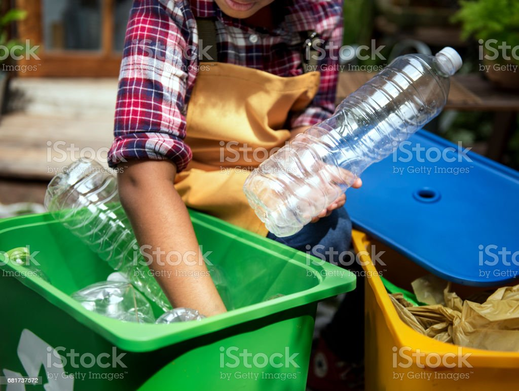 African Descent Kid Separating Recyclable Trash stock photo