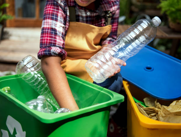 african descent kid separating recyclable trash - recycling symbol stock photos and pictures