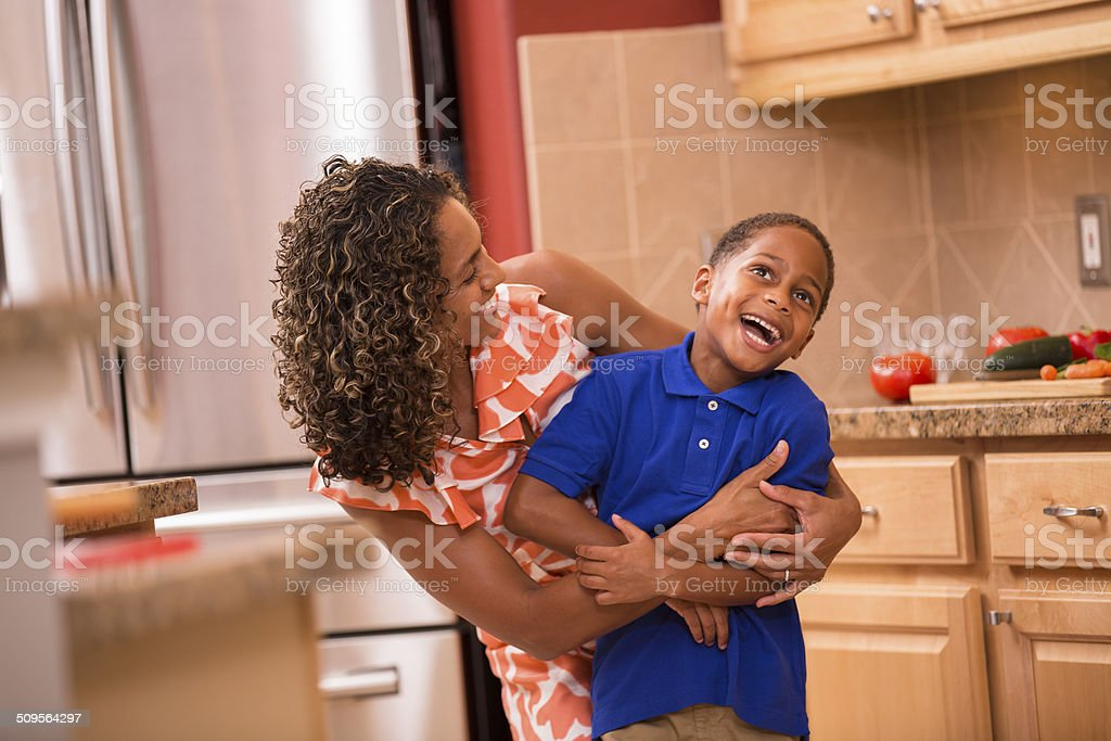 African descent little boy and mother hug, laugh home kitchen. stock photo