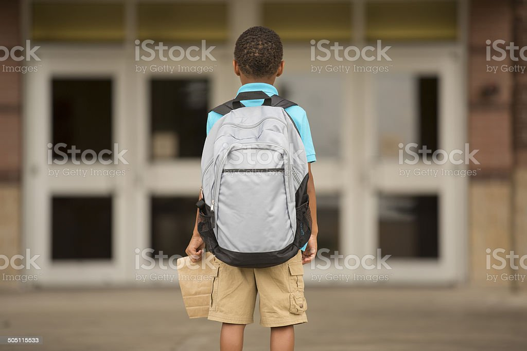 African descent, little boy faces school building. Lunch, backpack. royalty-free stock photo
