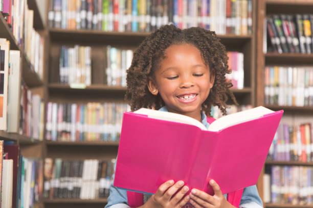afrikansk härkomst liten flicka i skolans bibliotek bok. - 6 7 år bildbanksfoton och bilder