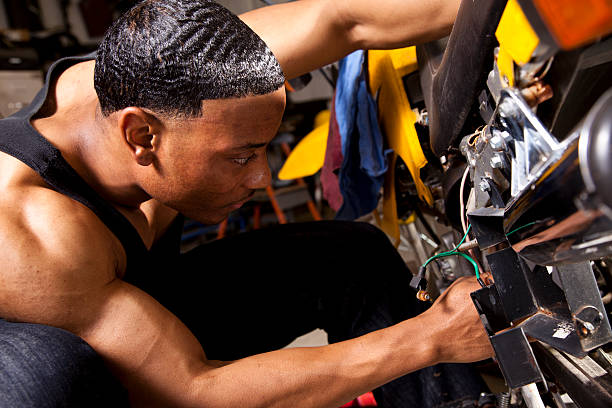 African descent man mechanic working on motorcycle. Repairs. stock photo
