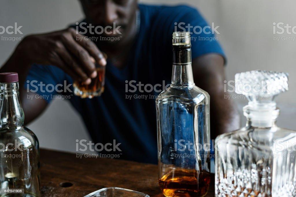 Homem de ascendência Africano sentado bebendo uísque dependência alcoólica mau hábito - foto de acervo