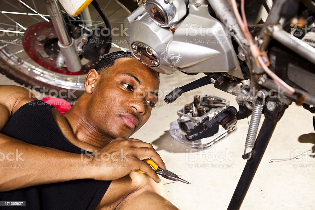 African descent man working on motorcycle repairs. stock photo