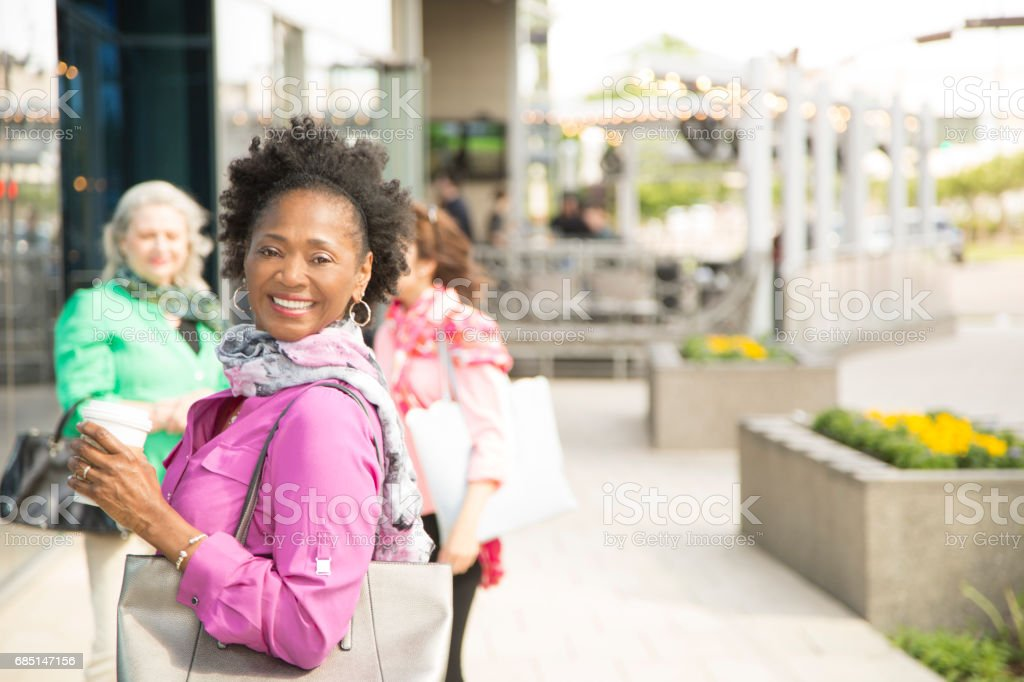 African descent, mature woman walking in downtown city area. royalty-free stock photo