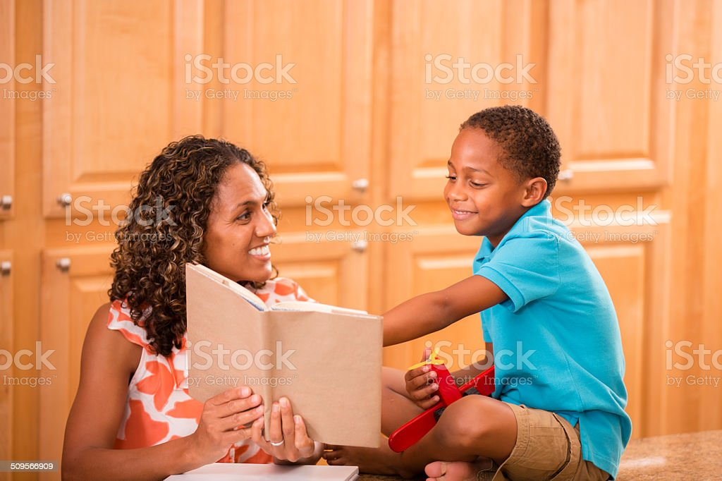 African descent mother and son doing homework together at home. stock photo