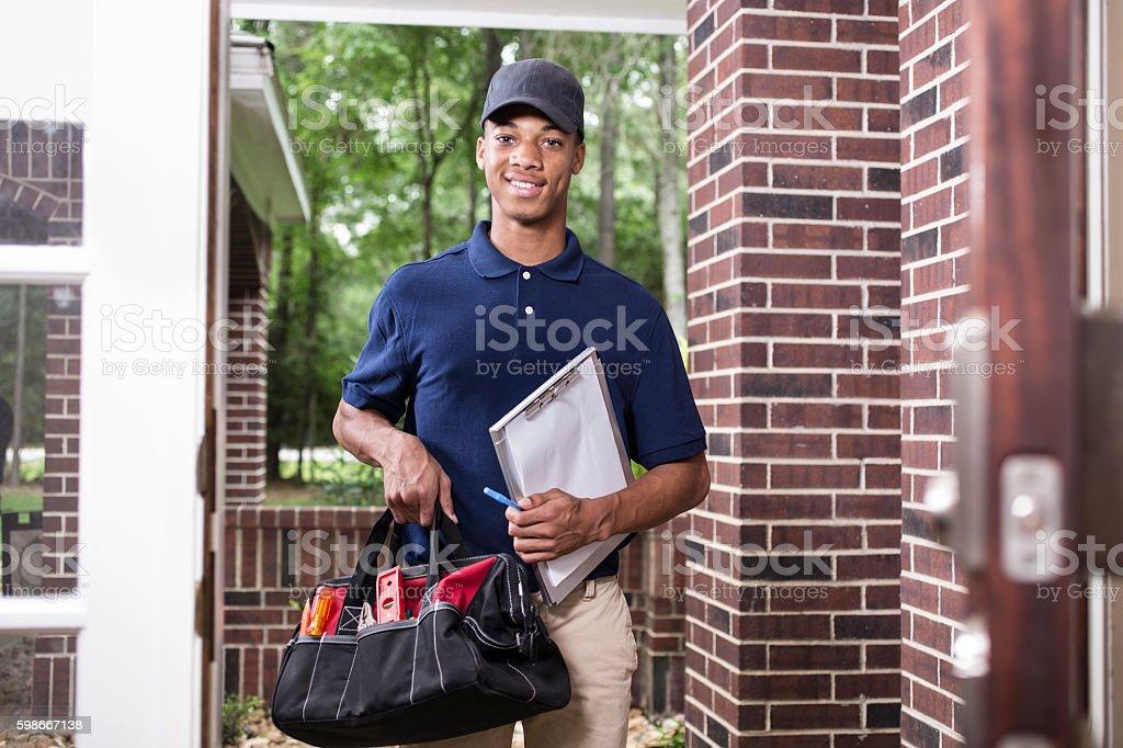 African descent repairman at customer's front door. – Foto