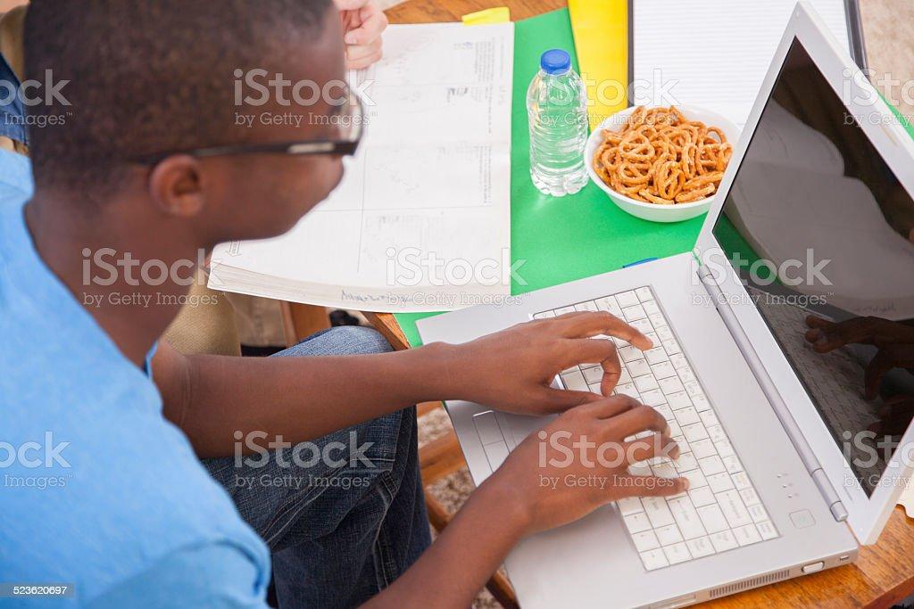 African descent teen boy studying. Home. Homework, laptop. Math book. stock photo