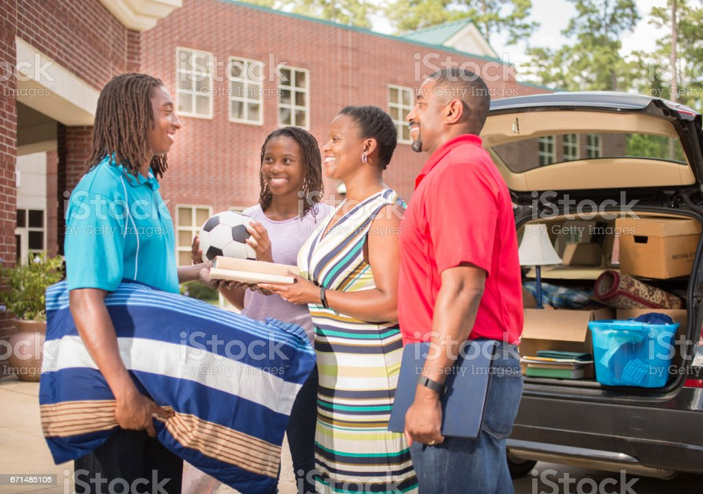African descent teenage boy moves into college dorm. stock photo
