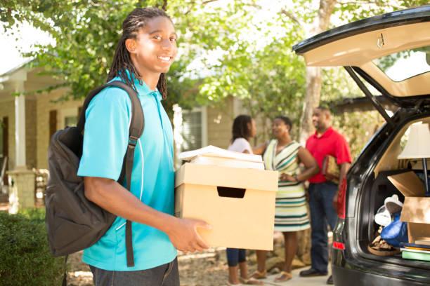 african descent teenage boy packs car to move to college. - oggetti personali foto e immagini stock