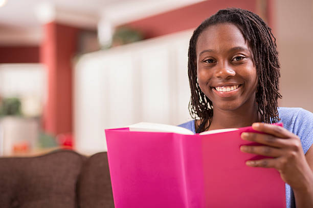 African descent teenage girl studying, reading book at home. African descent teenage girl studying or reading a book in home setting.  The high school student holds a pink textbook or novel as she looks up from her book toward the camera. Headshot.  Education themes. female high school student stock pictures, royalty-free photos & images