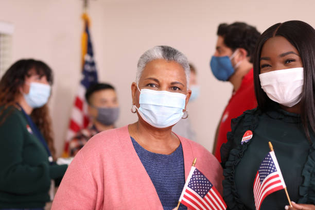 African descent women vote in USA election wearing mask. African descent women vote in the USA election wearing a protective mask to protect against COVID-19 or other infectious diseases.  Mother and daughter or friends. covid-19 stock pictures, royalty-free photos & images