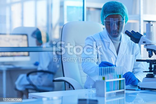 African young doctor in protective glasses working with samples while sitting at his workplace in front of microscope