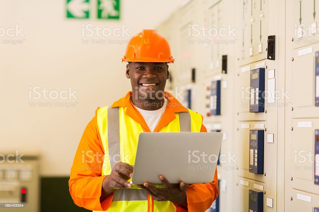 african electrical engineer with laptop computer in power plant stock photo