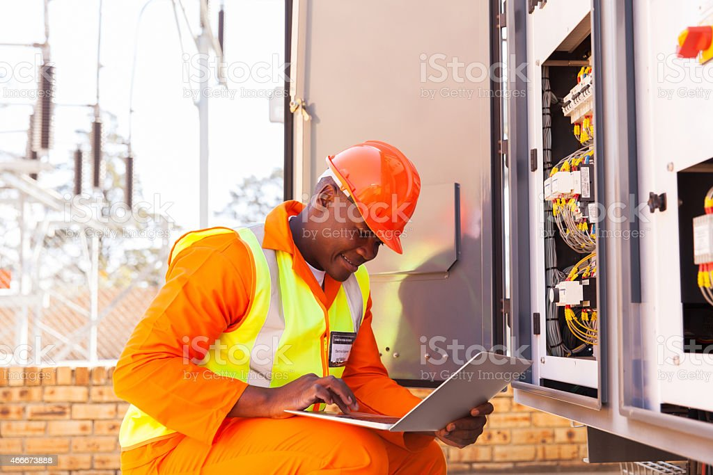 african electrical engineer working on laptop stock photo