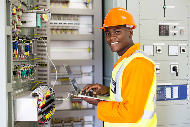 african electrical worker using laptop computer stock photo