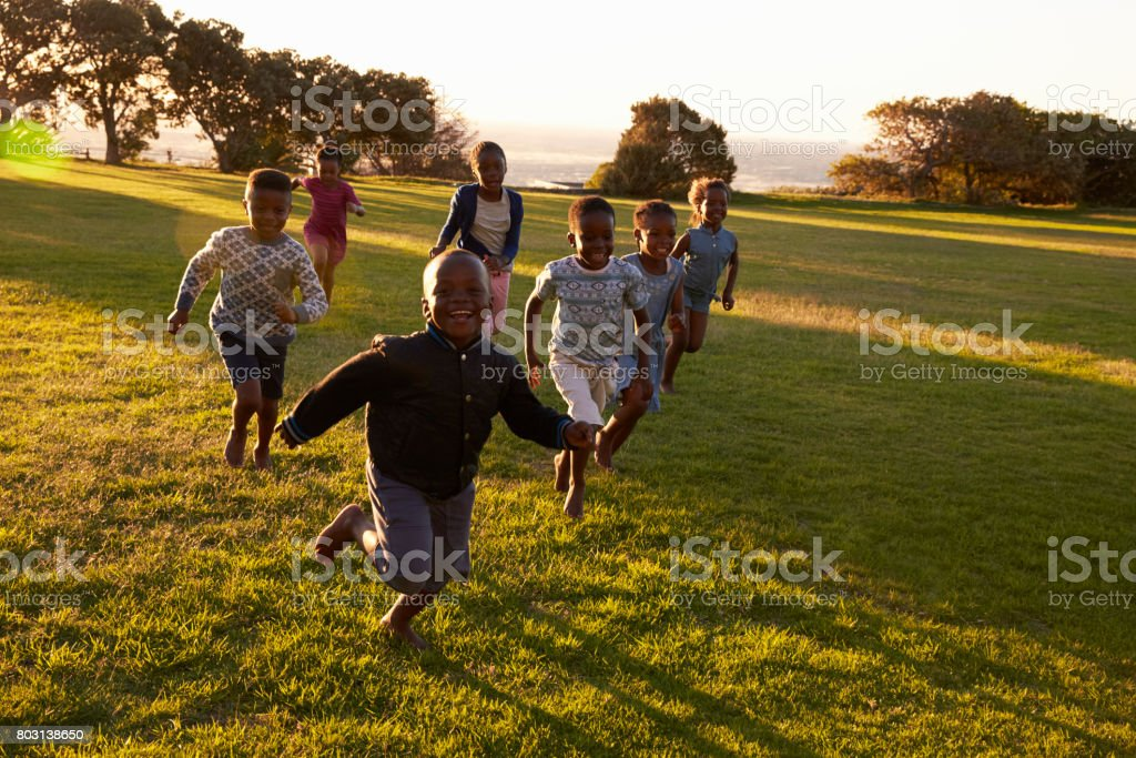 African elementary school kids running to camera in a field stock photo