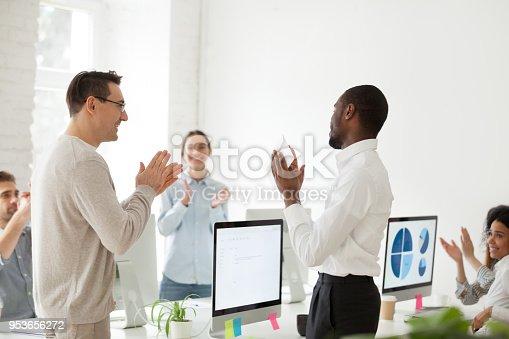918364538 istock photo African employee receiving envelope with bonus from boss, team applauding 953656272