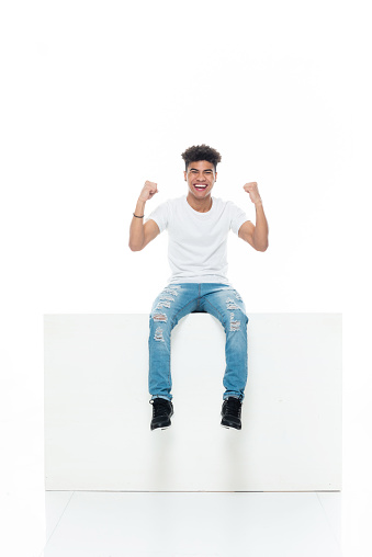African ethnicity boys sitting in front of white background wearing t-shirt