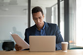 istock African ethnicity businessman checking documents using laptop working in office 1174262745