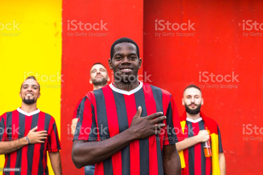 Football fan standing arms crossed in front of his friends,...