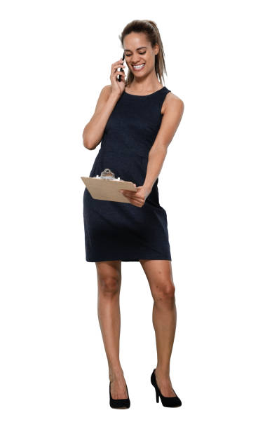 African ethnicity female manager standing in front of white background in the office wearing dress and holding contract and using mobile phone stock photo