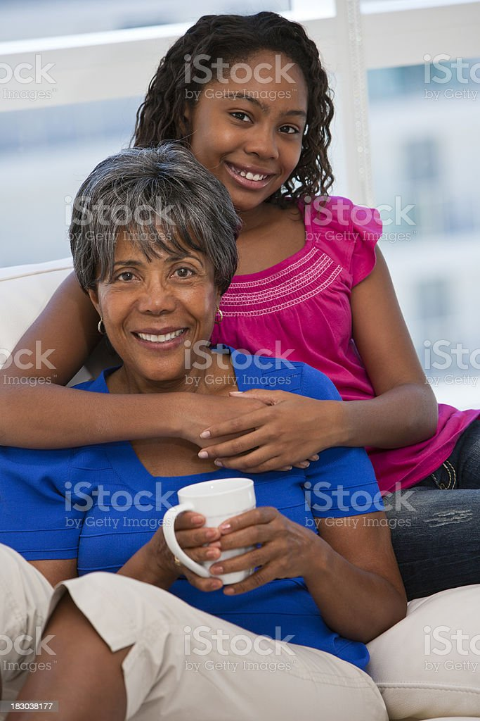 African ethnicity granddaughter hugging grandmother royalty-free stock photo
