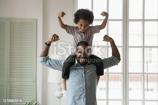 Small son sit on strong dad shoulders showing biceps. African family enjoy activity games at home, healthy fit lifestyle, two superheroes, vitamins for adults and children ad, happy Father Day concept