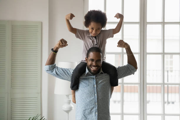African ethnicity little son sitting on fathers shoulders showing biceps stock photo