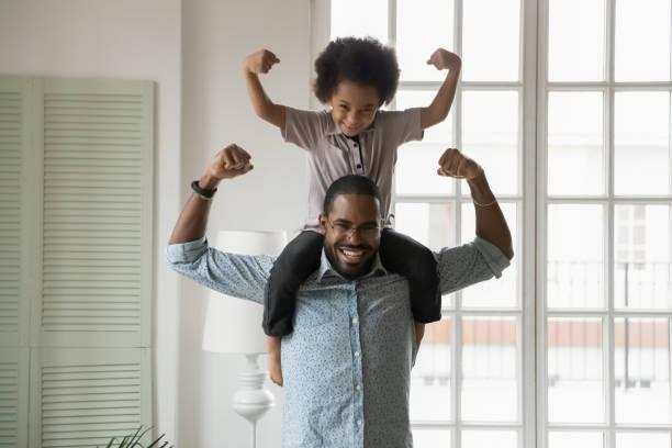 Etnia africana hijo pequeño sentado en los hombros de los padres mostrando bíceps - foto de stock