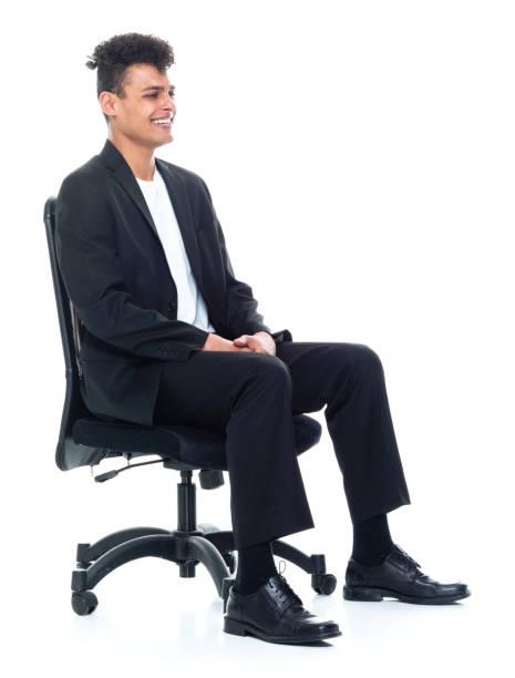ビジネスカジュアルを身に着けている白い背景の前に座っているアフリカの民族男性のビジネスマン - スマートカジュアル ストックフォトと画像