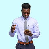 istock African ethnicity male business person standing in front of blue background wearing shirt and using smart phone 1209148825