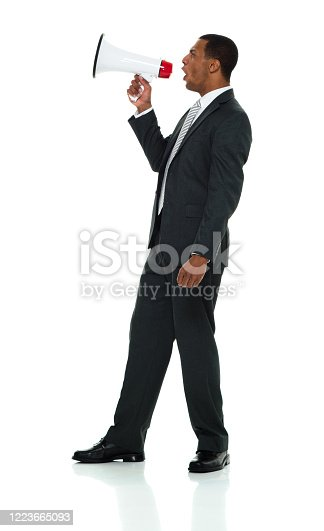 Front view of aged 20-29 years old african ethnicity male business person standing in front of white background wearing businesswear who is displeased and holding megaphone