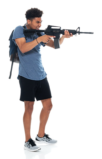 Profile view of aged 18-19 years old with curly hair african ethnicity male criminal standing in front of white background wearing sports shoe who is frustrated who is shooting - crime and holding weapon and using gun