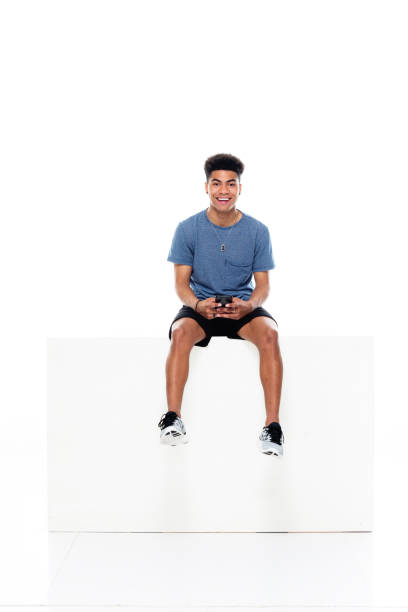African ethnicity male sitting in front of white background wearing t-shirt and holding box and using mobile phone stock photo