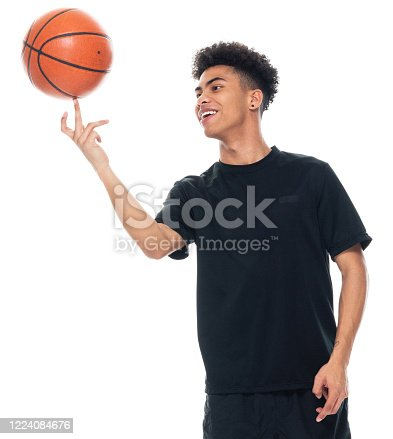 Front view of aged 18-19 years old with black hair african ethnicity male spinning in front of white background wearing sports clothing who is laughing and holding basketball - ball and using sports ball