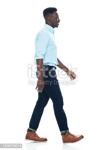 Full length of aged 20-29 years old with curly hair african ethnicity male walking in front of white background wearing jeans who is smiling