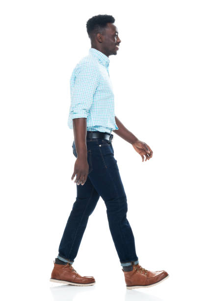African ethnicity male walking in front of white background wearing jeans stock photo