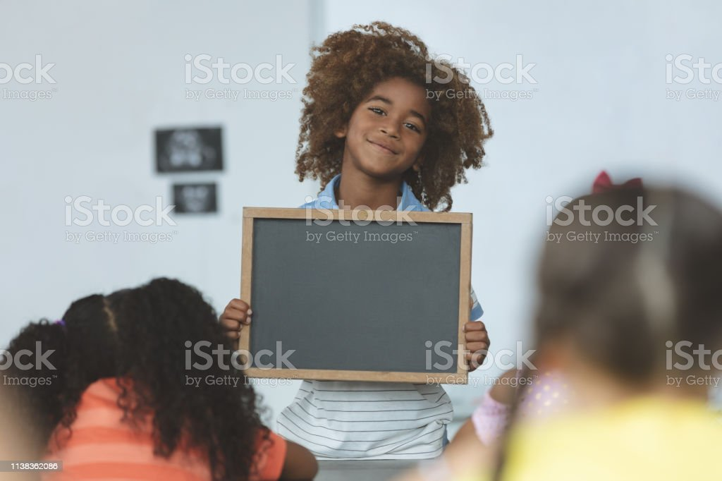 Front view of an Arican ethnicity schoolboy holding a slate and...